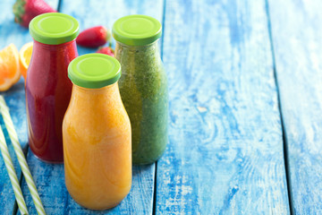 Fresh strawberry, orange and broccoli smoothie in bottles with fruits and vegetables on a blue wooden rustic background, close up and copy space
