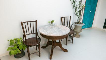 Stuhl mit Tisch vor weißer Wand mit Blumen