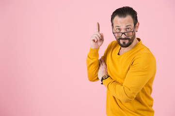 Clever man in glasses pointing up by finger. Bearded man notes by hand up. Wise man asks attention to above. Professor makes conclusion on pink background