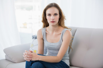 Stern young woman sitting on couch