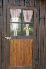 Tür eines Gartenhauses aus Holz mit eingelassenen Fenstern