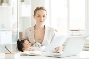 Young elegant business mother with papers sitting by workplace and holding her cute sleeping baby daughter