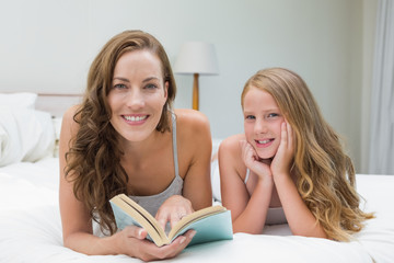 Girl and mother with book lying in bed