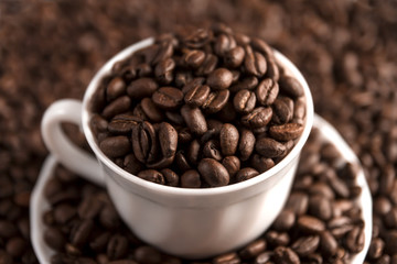Cup filled with coffee beans on coffee beans background. Selective focus.