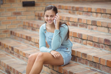 Happy schoolgirl sitting on staircase and talking mobile phone