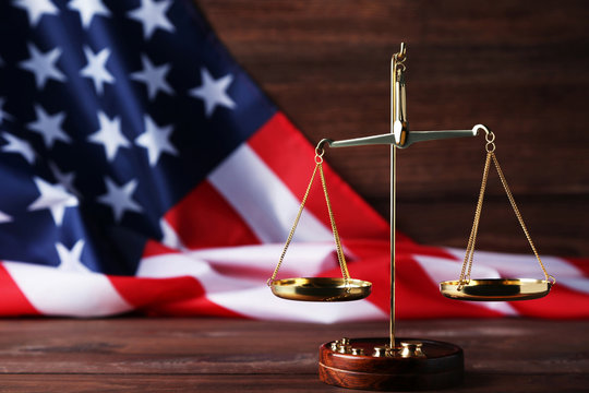 Scales of justice with american flag on brown wooden table