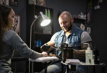 male tattooist preparing needle for filling machine for work wit