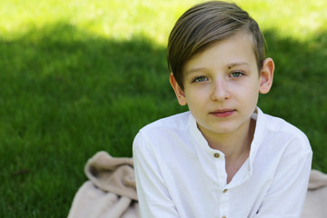 portrait of blonde boy dressed in white on the green grass