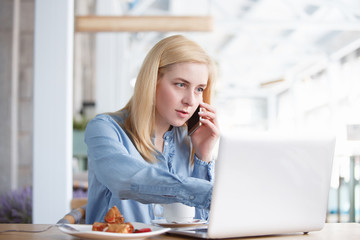 Pretty young woman outsourcing employee of large company working remotely sitting at table in cafe talking on smartphone with laptop using high-speed Internet