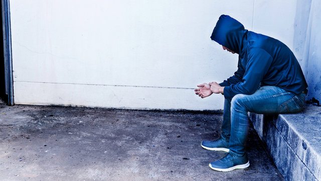 Man underhood addicted to drug sit alone in the abandoned building in downtown.