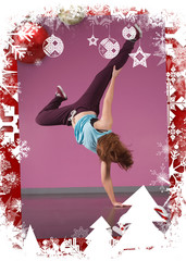 Pretty break dancer doing handstand with one hand against christmas themed frame