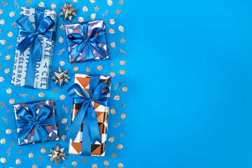 Gift boxes composition on blue background. Flat lay text space.