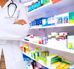 Mid section of a female doctor with skeleton model against close up of shelves of drugs
