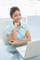 Elegant young businesswoman using laptop at office