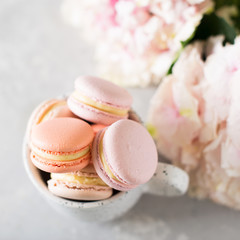 Spring mood still life with macaroons in cup and flowers