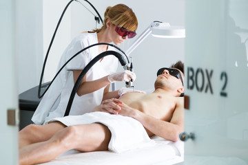 Young beautician removing torso hair with a laser to her client in the beauty salon.