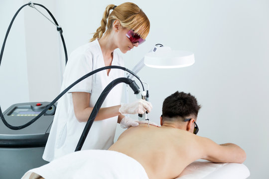 Young beautician removing back hair with a laser to her client in the beauty salon.