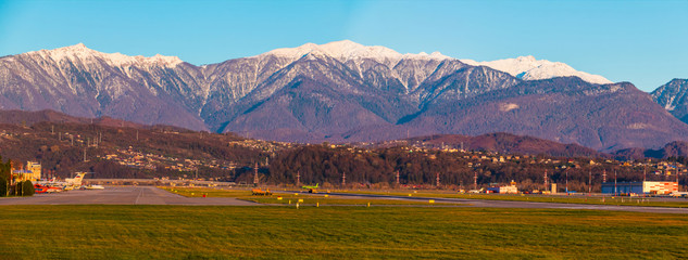 Panoramic view of the airdrome of Sochi International Airport on the background of mountains in sunny day, Adler, Sochi, Russia