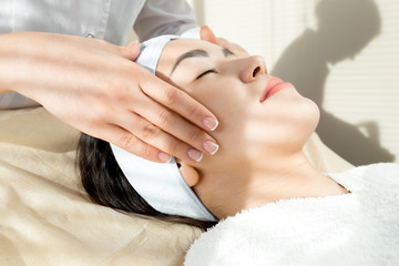 Side view portrait of pretty Asian woman enjoying relaxing face massage during beauty treatment  in modern cosmetology office