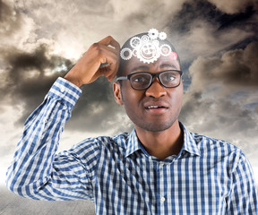 Young businessman thinking scratching head against blue sky