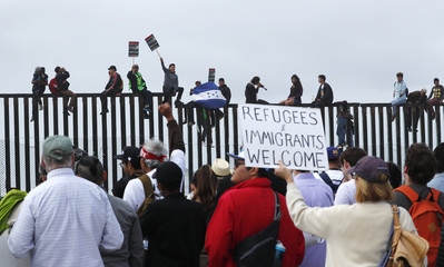 People climb the border wall fence as a caravan of migrants and supporters reached the United States-Mexico border near San Diego