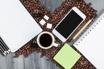 Wooden workplace with smartphone and coffee