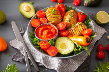 vegan buddha bowl. healthy lunch bowl with hasselback potato, avocado, tomato, bell peppers and pepper sauce