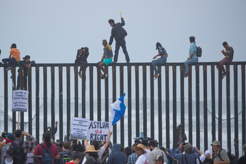 People in Mexico climb the border wall fence as a caravan of migrants and supporters reached the United States-Mexico border near San Diego, California