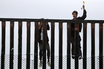Members of a migrant caravan from Central America and their supporters climb up the U.S.-Mexico border wall at Border Field State Park before making an asylum request, in San Diego
