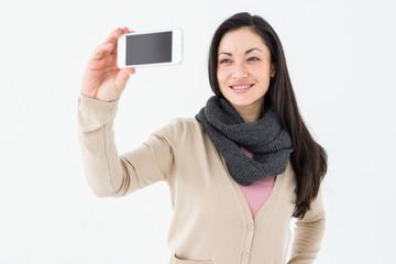 Smiling brunette taking selfie