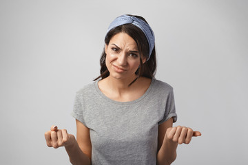 Human reaction, facial expression, attitude and life perception. Picture of dissatisfied annoyed young female wearing headband clenching fists and frowning, having questioning displeased look