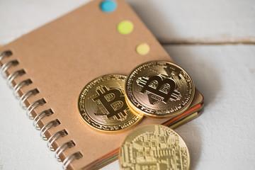 Bitcoin Münzen auf Notizblock und weißem Holzuntergrund