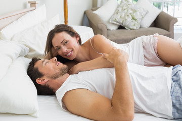 Happy relaxed couple together in bed