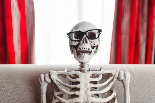 Smiling skeleton in glasses is sitting on couch