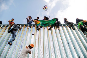 Members of a caravan of migrants from Central America sit on the border fence between Mexico and the U.S., as part of a demonstration prior to preparations for an asylum request in the U.S., in Tijuana