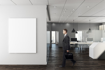 Businessman in modern office with empty wall