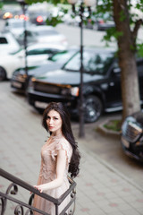 fashionable pretty girl in summer dress on background of city streets with expensive cars and green trees outdoor