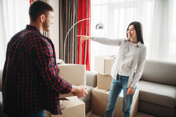 Happy couple arrange cardboard boxes on a room