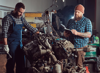 Two bearded mechanics specialist repairs the car engine which is raised on the hydraulic lift in the garage.