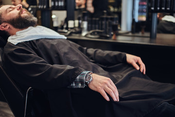 Handsome bearded male waits for the hairdresser sitting on a barber chair.