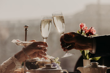 Man and woman celebrate wedding, have party with friends, clink glasses with sparkling wine or champagne. People, celebration and festive event concept