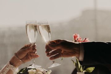 Female`s and male`s hands hold glasses with sparkling champagne, clink and toast, celebrate special festive event in their life. Celebration concept