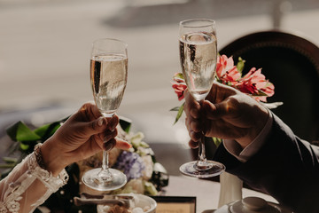 Close up image of glasses of champagne or wine, clink glasses, celebrate together their wedding day, hve festive event. People, dating and celebration concept