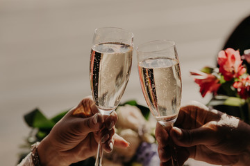 Bride and groom toast and clink glasses with champagne, celebrate wedding in restaurant. Engaged young couple celebrate this special occasion.
