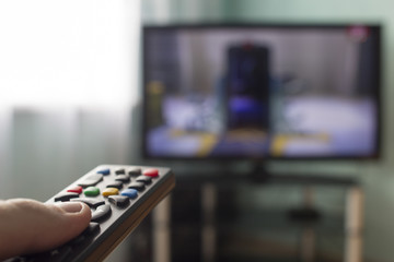 In the hands of the remote from the TV, in the background comes the TV