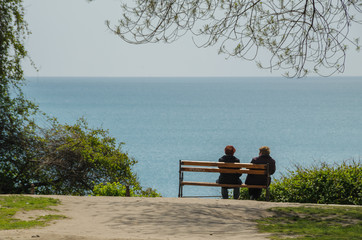 Two elderly women are sitting on the bench in the park and  looking at the sea. Concept of peasful and calm retired life.
