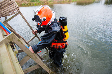 Diver in a diving suit and helmet ready to dive