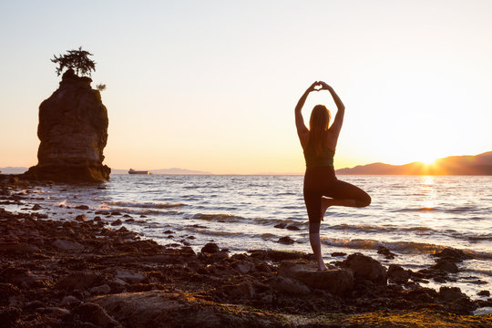 Young Woman practicing yoga on a rocky shore during a vibrant sunset. Taken in Stanley Park, Vancouver, British Columbia, Canada.