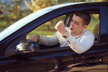Young impatient man is yelling at the cars in front of him