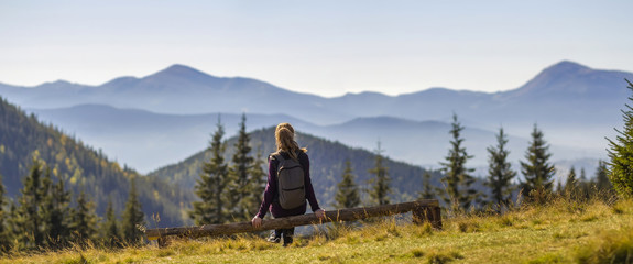 Back view of long-haired blond girl with backpack sitting on broken tree trunk enjoying breathtaking view of magnificent foggy Carpathian mountains, covered with ever-green forest on spring morning.